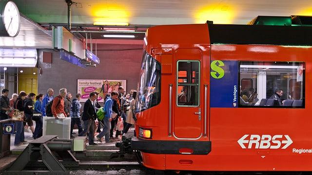 Ein Zug der RBS steht im Bahnhof, viele Leute wollen einsteigen.