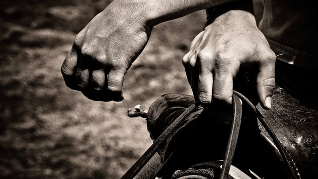 Hände eines Cowboy über einem Sattel.