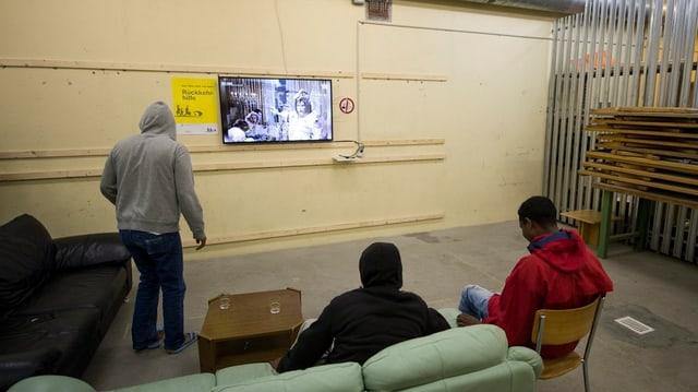 Drei Männer sitzen auf dem Sofa und schauen TV.
