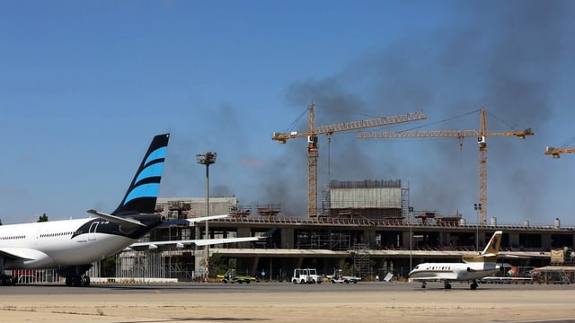 Rauch und kaputtes Gebäude, ein halbes Flugzeug davor.