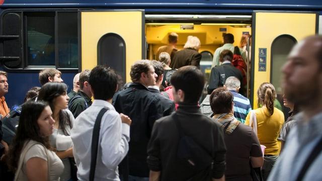 Passagiere am HB Zürich steigen in eine S-Bahn ein.