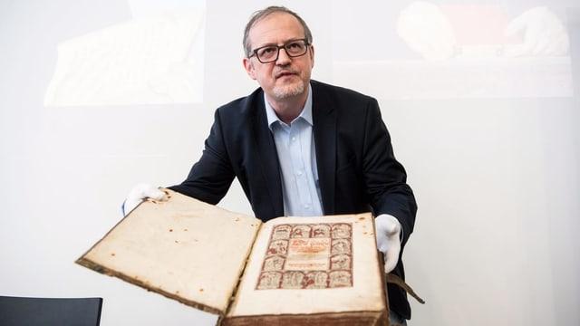 Ein Mann mittleren Alters mit schwarzem Jakett und hellblauem Hemd hält ein altes Buch in der Hand. Auf dem Buch ist eine illustration ersichtlich und die Spuren seiner Vergangenheit klar erkennbar.