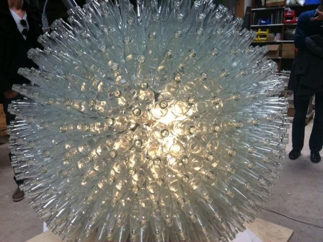 Eine Kugel aus Glasflaschen, von innen beleuchtet.