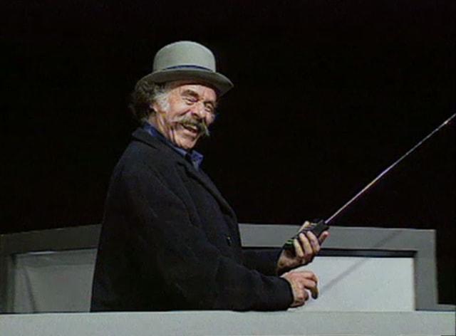 Mann mit Hut vor schwarzem Hintergrund.