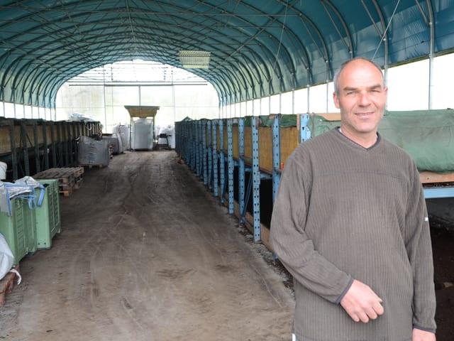 Ein Mann vor blauen Lagerregalen.