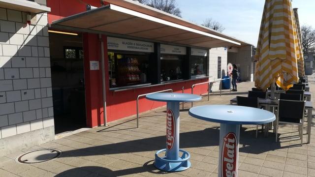 Kiosk mit Tischen, Stühlen und Sonnenschirmen.