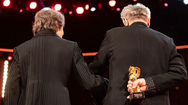 Eine Frau und ein Mann stehen mit dem Rücken zur Kamera, er hält einen goldenen Bären