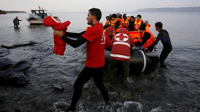Ein Mitarbeiter des Roten Kreuzes trägt ein Baby von einem Flüchtlingsboot.