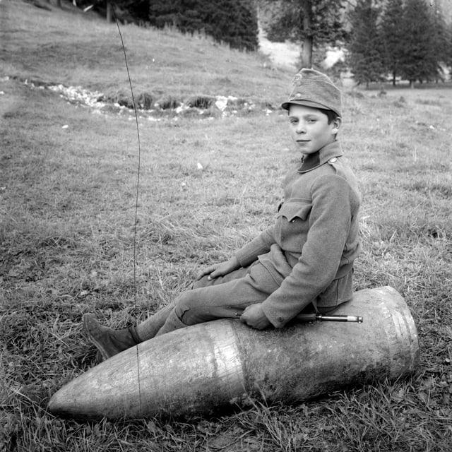 Ein Kind sitzt auf einer Granate.
