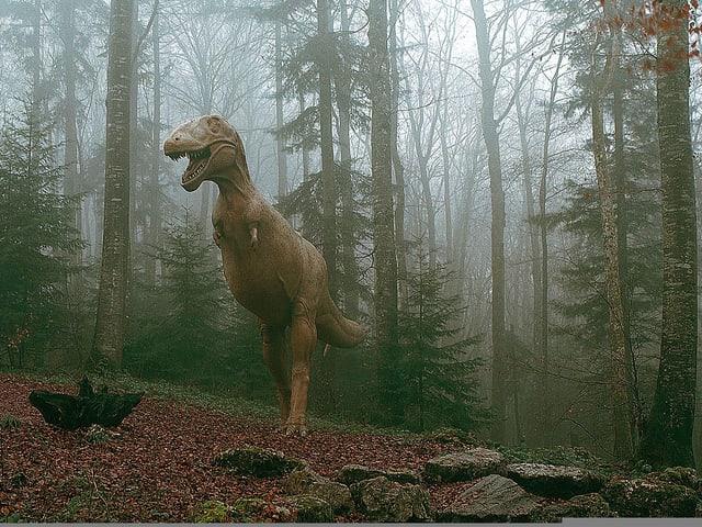 Figur eines Tarbosaurier im herbstlichen Wald.