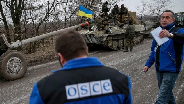 Dus umens cun giaccas blauas da la OSCE che guardan sin in tanc cun schuldads e bandiera da l'Ucraina.