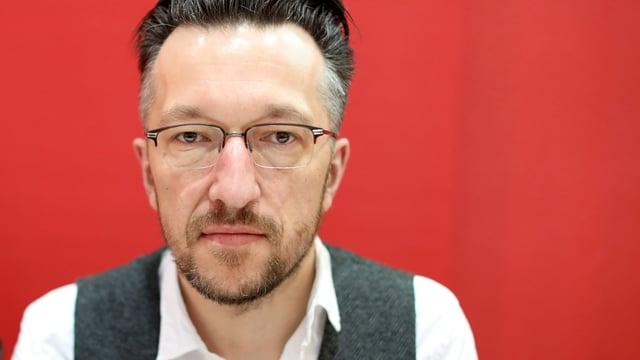 Ein Mann mit Brille blickt in die Kamera.