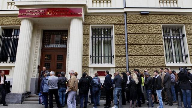 Leute warten vor der verschlossenen Türe einer Bank.