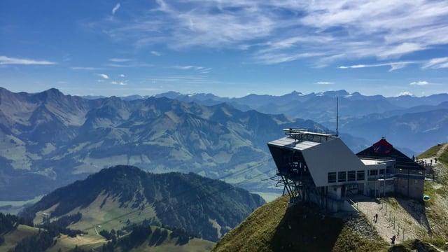 Blick auf die Bergstation der Bahn am Moléson und dahinter das Bergpanorama.