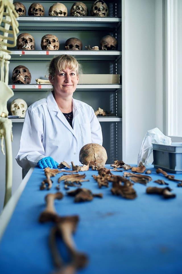 Eine Frau im forensischen Institut. Vor ihr liegen Knochen.