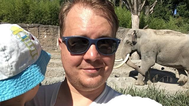 Ein junger Mann mit Sonnenbrille und Kind auf dem Arm macht ein Selfie. Im Hintergrund ein Elefant im Zoo.