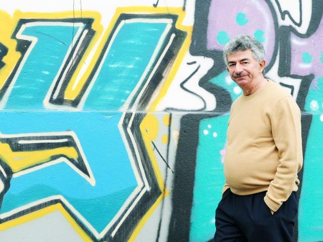 Ein graumellierter Herr steht in gelbem Strickpulli vor einer Wand mit Graffiti.