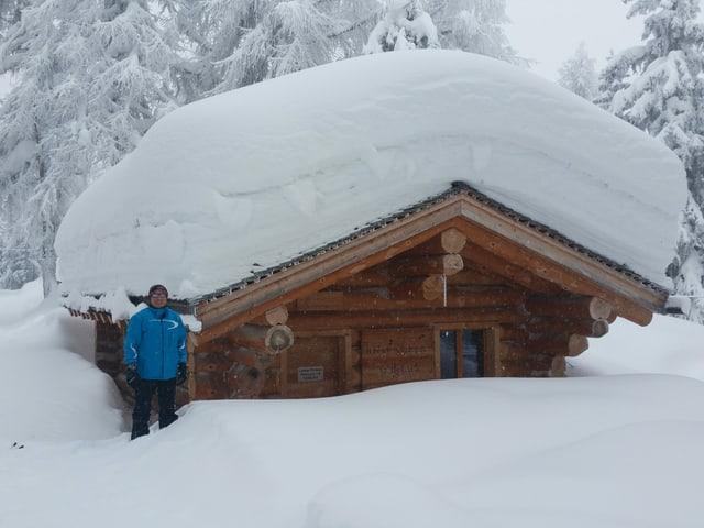 Mann vor Haus. Auf dem Haus viel Schnee.