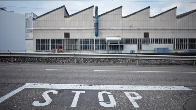 Ein Fabrikgebäude. Davor eine Strasse mit einem Stoppsignet.