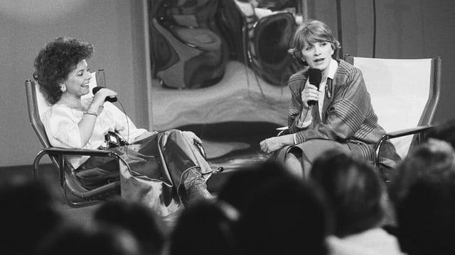Heidi Abel und Nella Martinetti in tiefen Sesseln. Davor unscharf die Köpfe des Publikums.