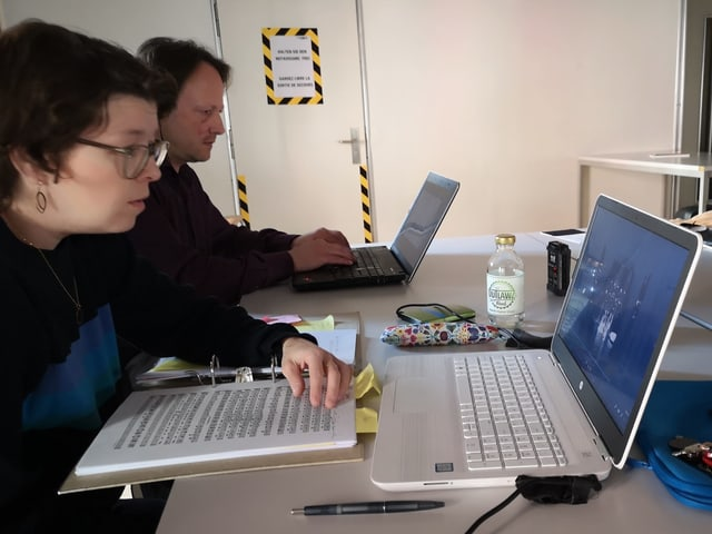Zwei Personen vor Laptops.