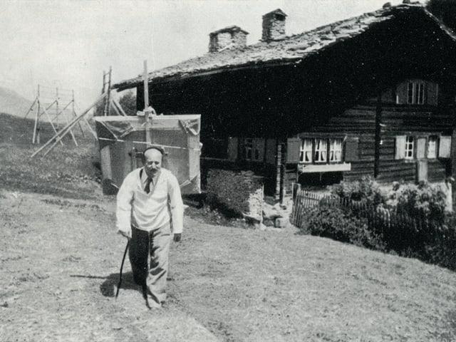 Alois Carigiet viandant cun in maletg enramà sin sia catla