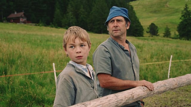 Ein Bub und sein Vater stehen an einem Zaun.