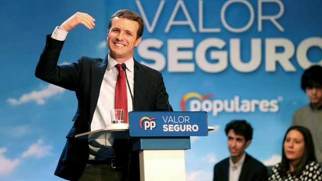 Pablo Casado spricht an einer Wahlkampfverantsaltung. Er trägt einen schwarzen Blazer, rote Krawatte und hebt die rechte Hand.