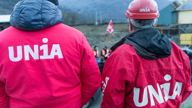 Zwei Männer in roten Jachen der Gewerkschaft Unia von hinten fotogografiert