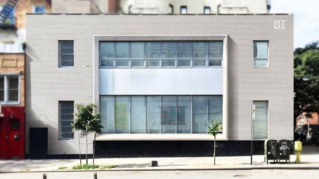 Ein hellgraues kubistisches Gebäude mit vielen Fenstern.