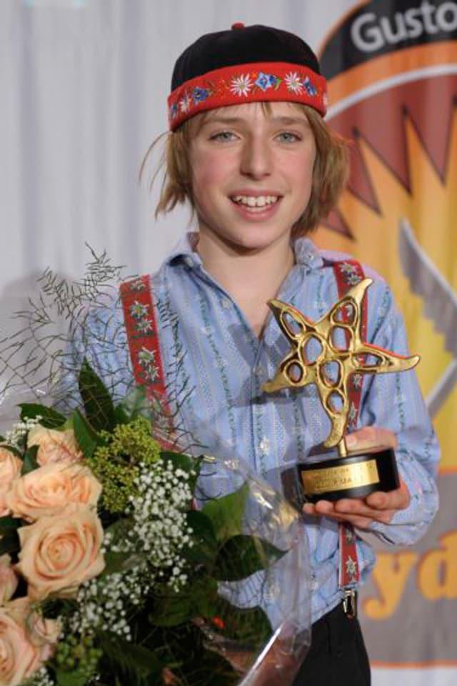 Oliver Marti mit Blumenstrauss und dem Kleinen Prix Walo in den Händen.