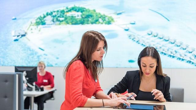 Zwei junge Frau beugen sich an einem Tisch über ein Tablet.