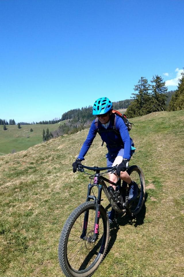 Purtret da Caduff, co ella va cun in mountainbike.