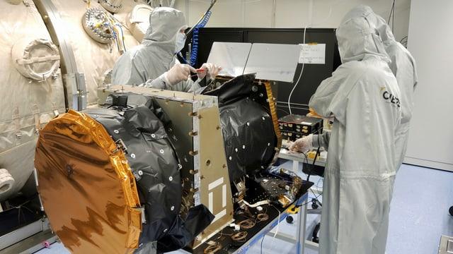 Wissenschaftler in Overalls arbeiten am Cheops-Satelliten