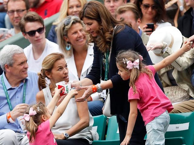 Mirka Federer den ZWillingen Charlene und Myla auf der Tribüne.