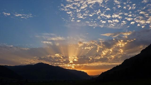Die Sonne geht hinter einem Hügelzug unter. Am Himmel erkennt man die Strahlenbündel der untergehenden Sonne. Man nennt das Phänomen aus Tyndall-Effekt.