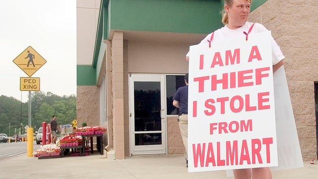 """Ladendiebin mit einem umgehängten Schild """"I stole from Walmart"""""""