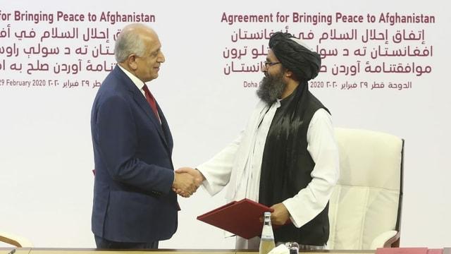 Der Friedensgesandte der USA, Zalmay Khalilzad (links), und der Taliban-Beauftragte Mullah Abdul Ghani Baradar nach der Unterzeichnung eines Abkommens zwischen beiden Seiten.