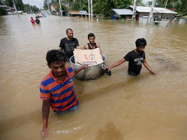 Vier Männer waten durch eine überflutete Strasse.