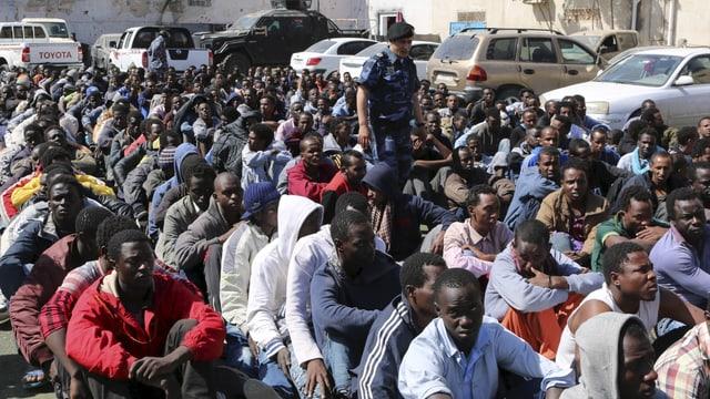 Illegale Migranten sitzen am Hafen von Tripolis, bewacht von der libyschen Marine (Oktober 2016)