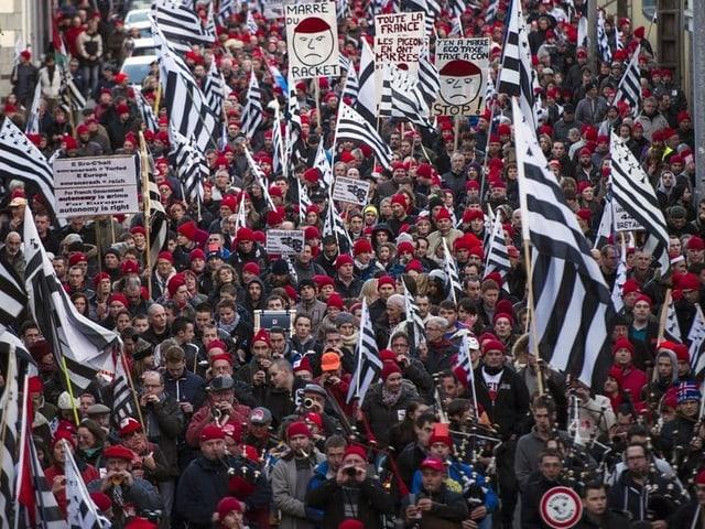 Demonstranten mit roten Mützen.