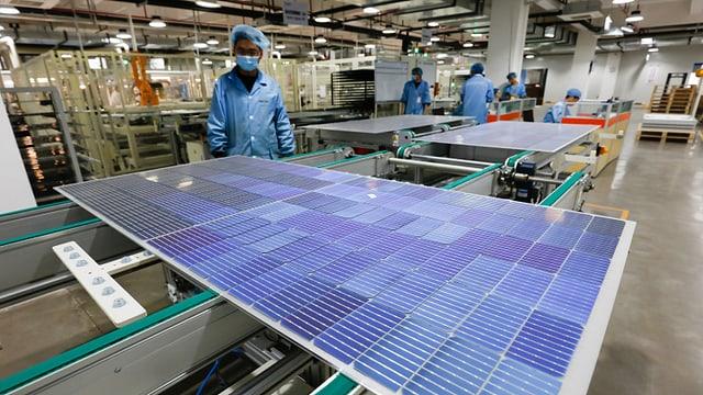 Arbeiter in chinesischer Firma steht vor Solarpanel
