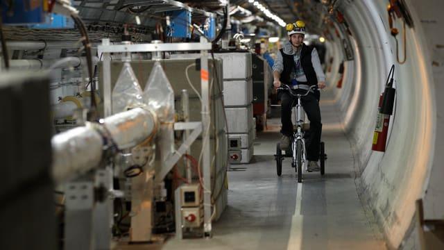 Ein Mann mit Helm fährt auf einem Dreirad durch einen Tunnel des Large Hadron Collider des Cern.