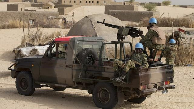 Auf dem Deck eines Pick-ups befinden sich drei UNO-Blauhelmsoldaten mit schweren Waffen.