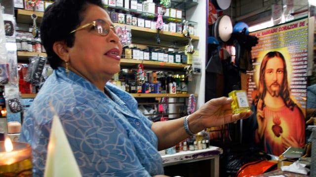 Eien Frau in einem Kiosk. Im Hintergrund ist ein Jesus-Plakat.