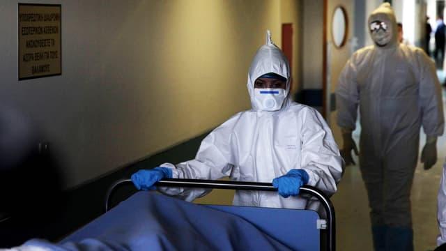 Krankenhauspersonal in Schutzkleidung schiebt ein Bett durch den Gang.