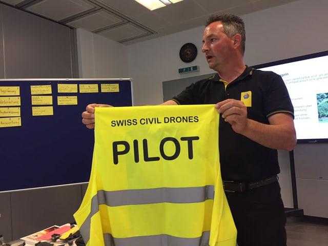 Mann präsentiert eine gelbe Warnweste.
