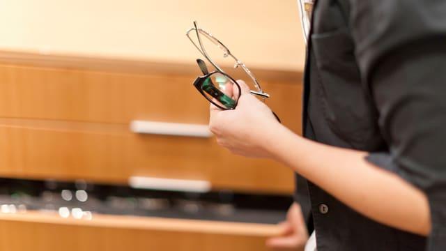 Ein Optiker mit mehreren Brillen in der Hand vor einem Schubladengestell.