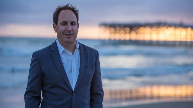 Stephan Aarstol im Anzug am Strand