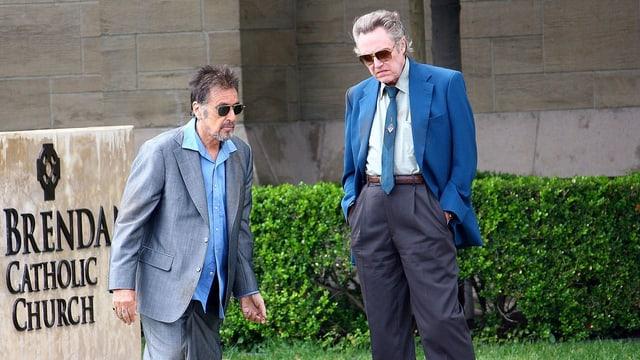 Zwei Männer in Anzügen stehen nebeneinander